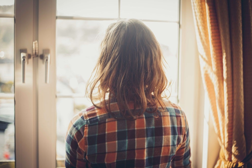 woman stares out of a double glazed window