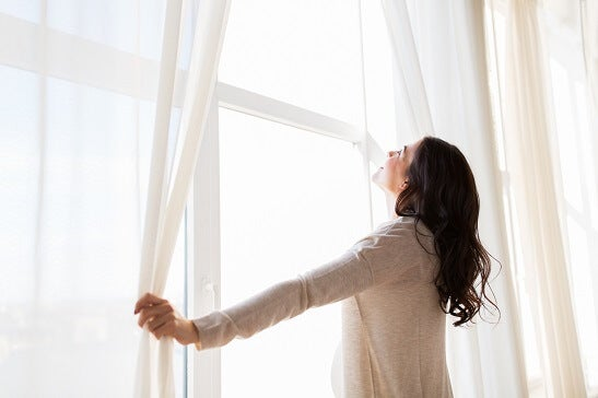 Woman looks out of double glazed windows