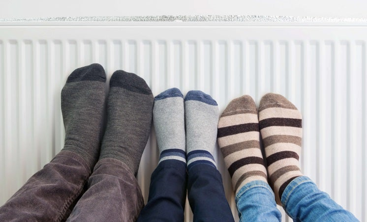 Three people put their feet on a radiator powered through a boiler