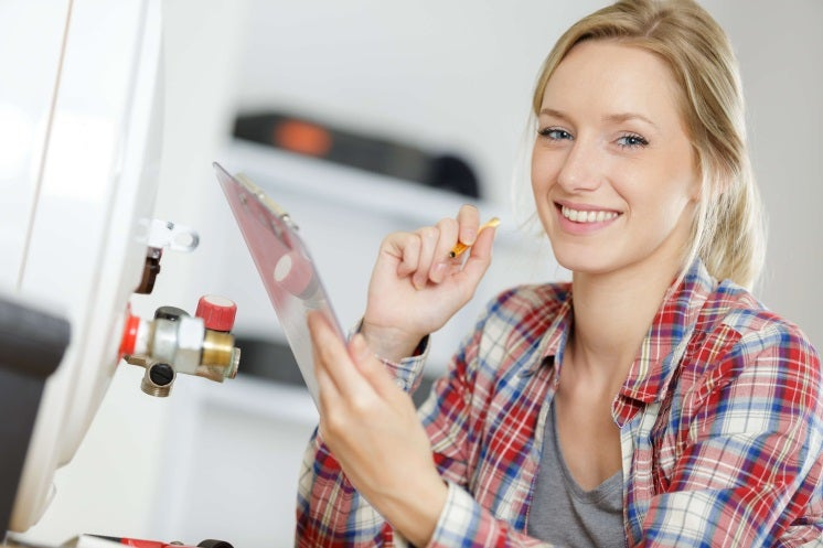 woman looks at camera as she's installing a boiler