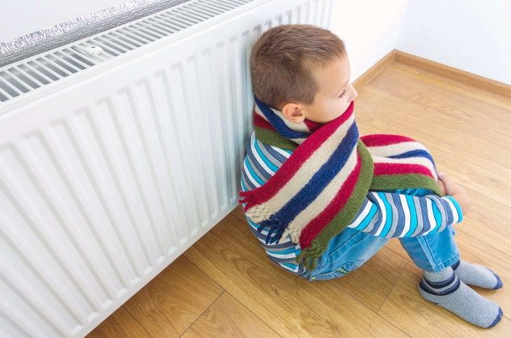 child leaning against radiator