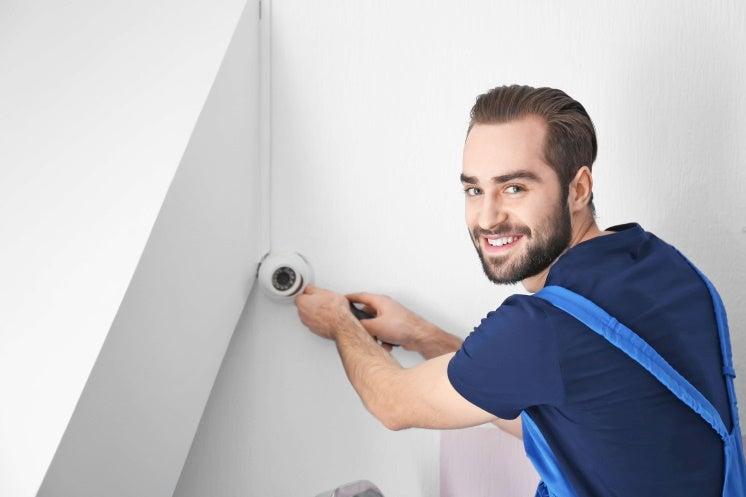 man installs a home security alarm