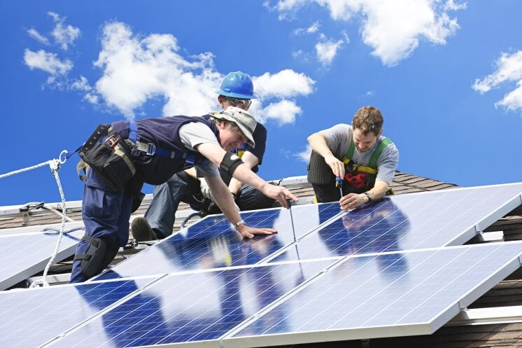 three people install home solar panels