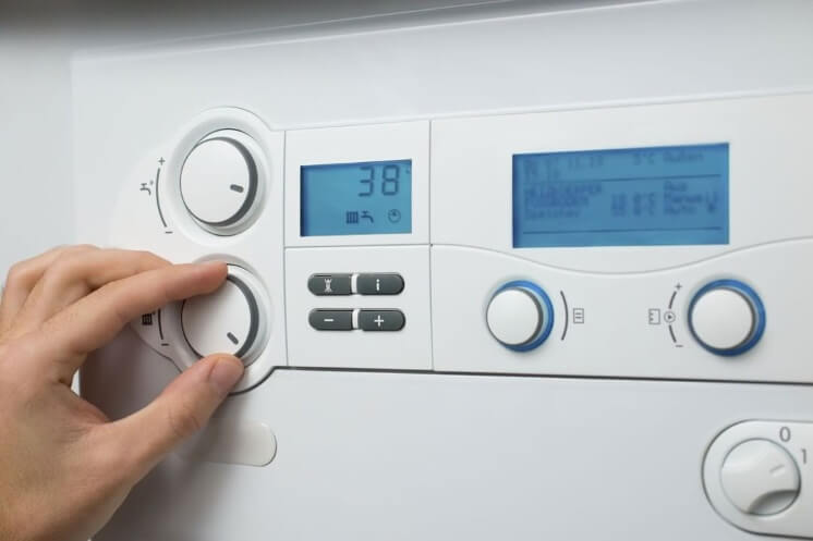 a person changes a boiler's temperature