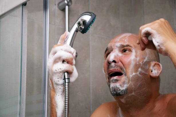 a man looks aghast after his hot water supply shuts off