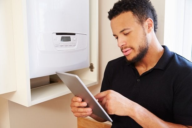a man uses his tablet as he installs a boiler