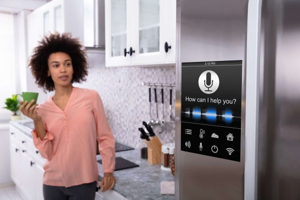 a woman interacts with her smart home fridge