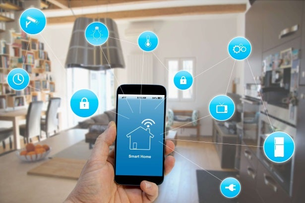a man accesses his phone's smart home app as icons swirl around him