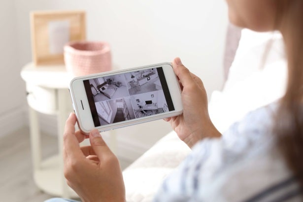 a woman looks at her phone to check what her smart security home cameras are seeing
