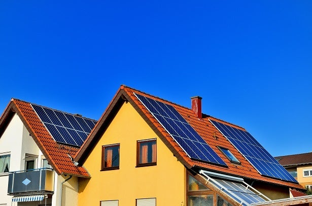 solar panels on top of a yellow house