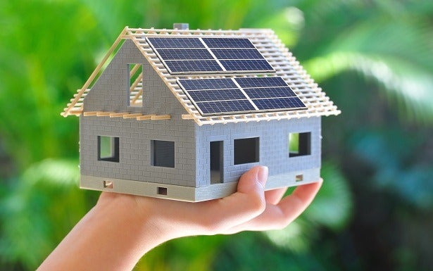 a small model house with solar panels on the roof