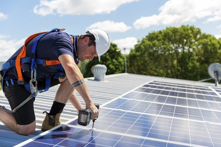 solar panel installer on a roof