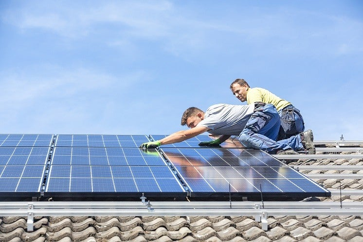 solar panel installers on a roof