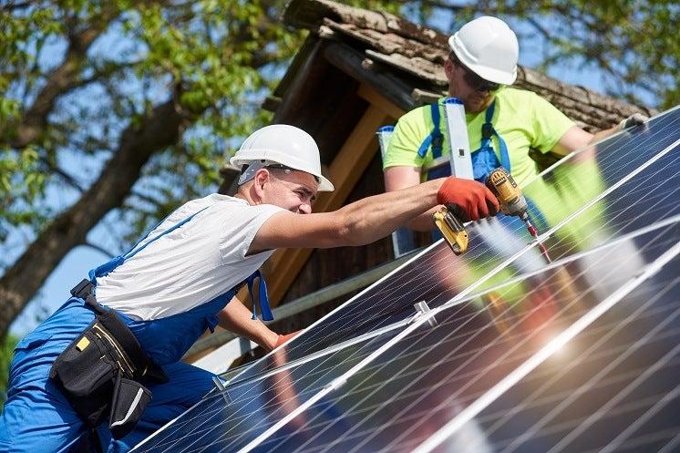 men repairing solar panels