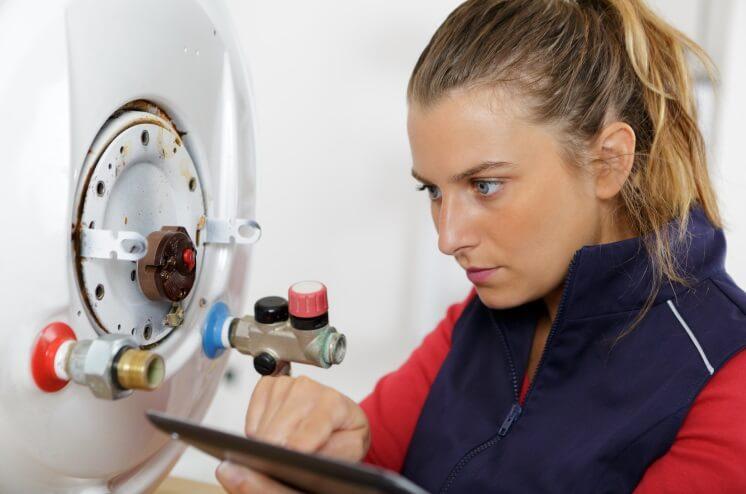 female boiler technician works on a boiler
