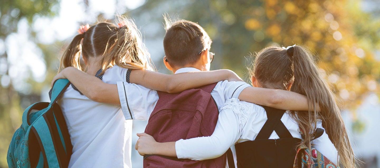 schoolchildren with their arms around each other