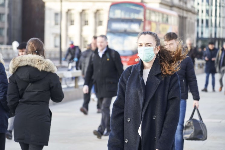 woman walking with a mask on in central london