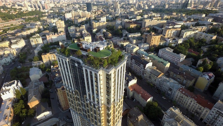 a tower in a city with a green roof