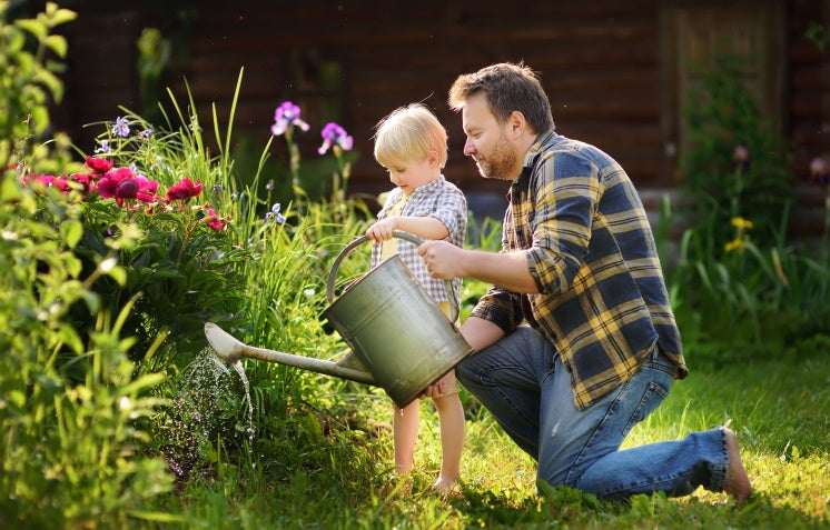 father and son water their garden