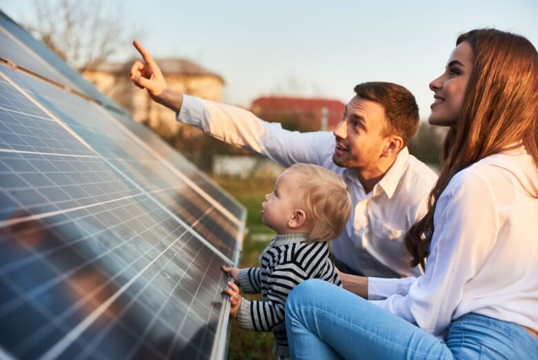 man, woman and child look at solar panels