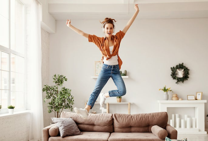a woman jumping on sofa after energy switching