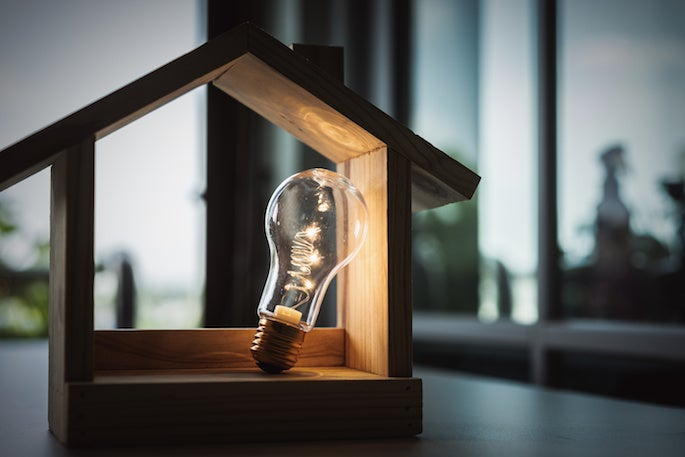 lightbulb inside a model wooden house