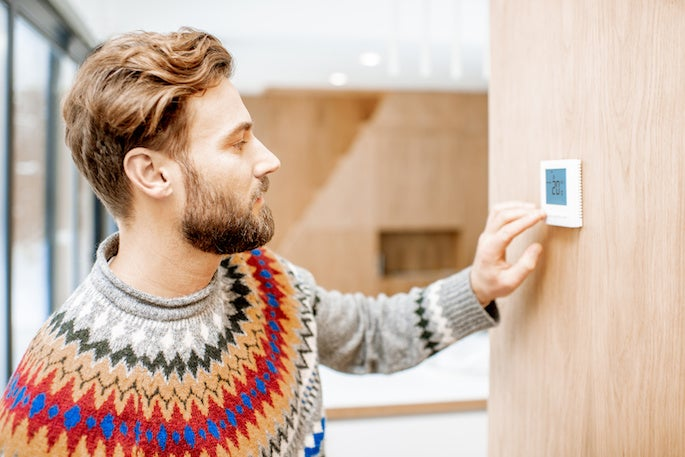 bearded man in jumper changing thermostat