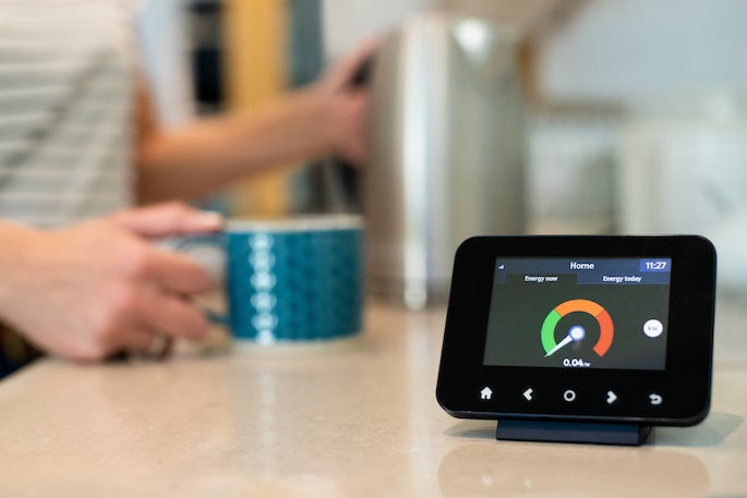 a man has a coffee next to his smart meter at home
