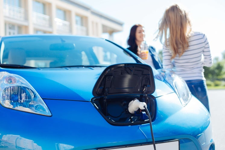 two women standing next to a charging electric car