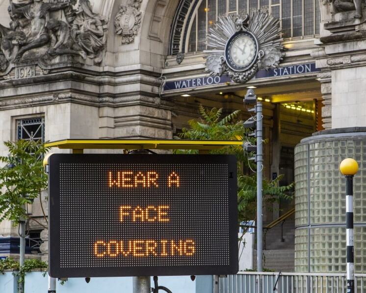 "a COVID-19 sign outside Waterloo Station, reading ""wear a face covering"""