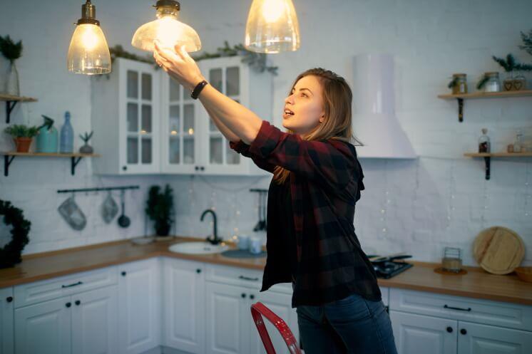person installs light bulb in their kitchen