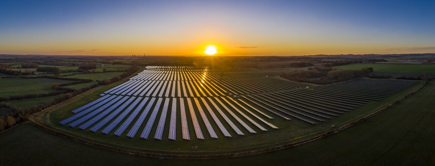 the sun rises over solar panels in the UK