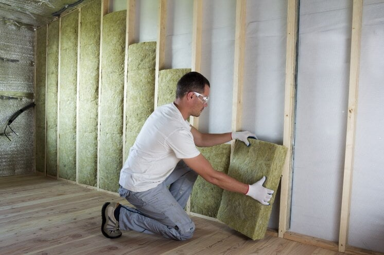 professional installs solid wall insulation using a stud wall