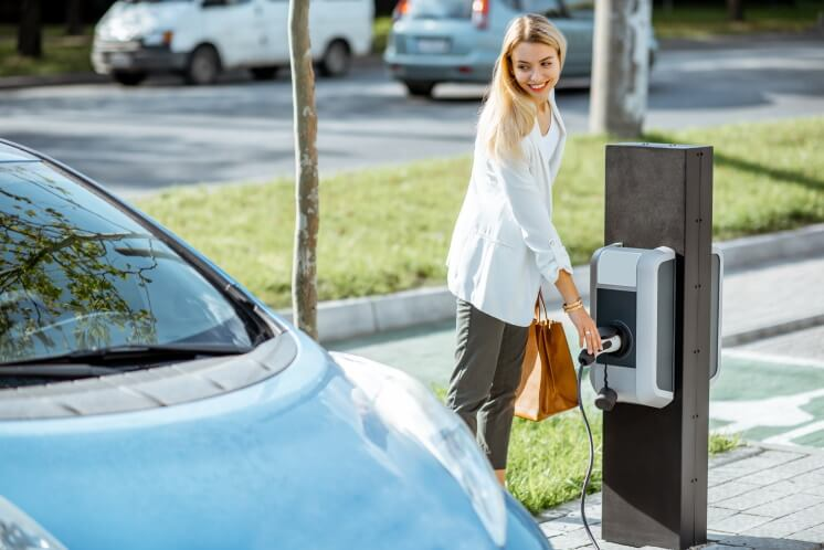 woman charging her electric vehicle