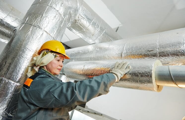 woman fitting pipe insulation
