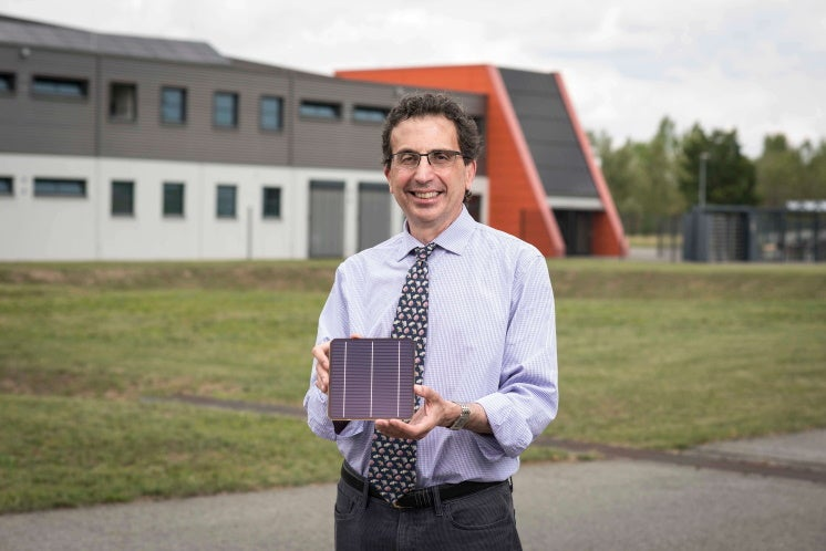 Dr Chris Case outside Oxford PV's German factory, holding a perovskite tandem solar cell