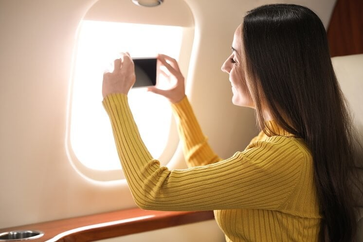 woman taking photo out of plane window