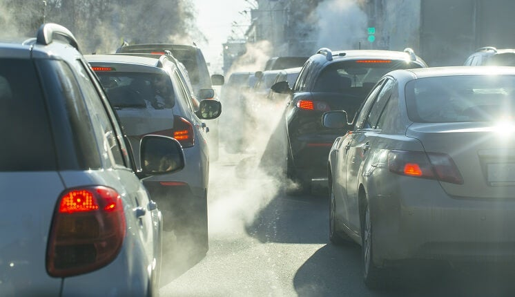 cars releasing emissions on road