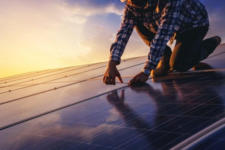 man installs solar panels