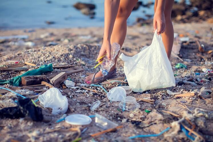 someone picking up litter on beach
