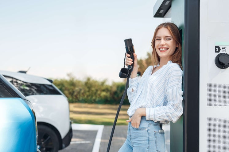 woman holding electric car charger