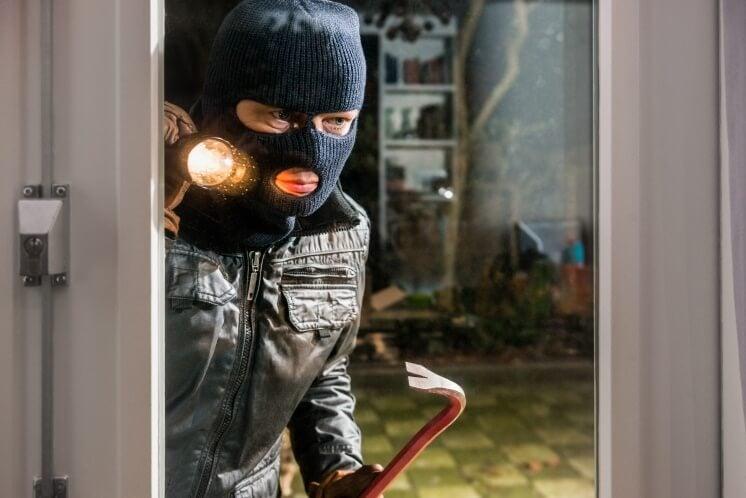 burglar with a crowbar looks into a home