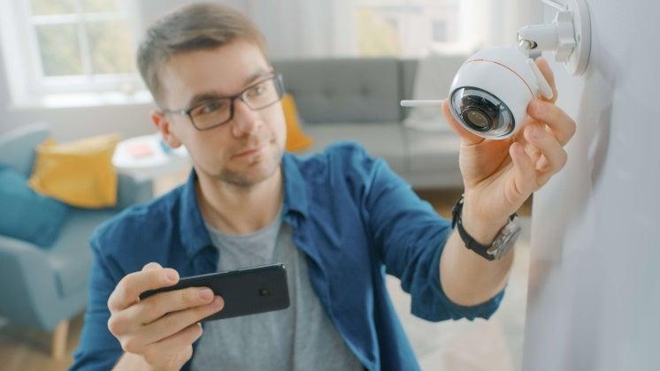 man adjusting his security camera