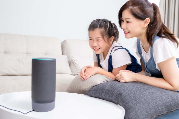 mother and daughter look at smart speaker