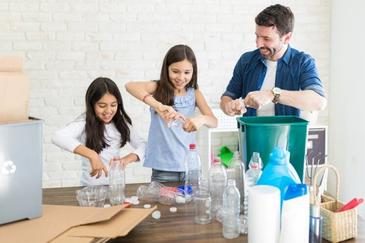 man and two girls recycling at home