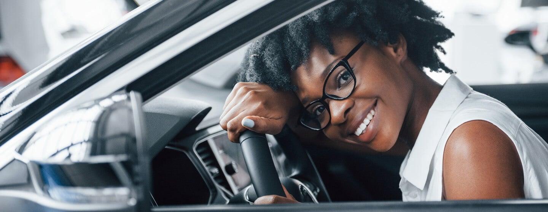 woman resting head on wheel of new car