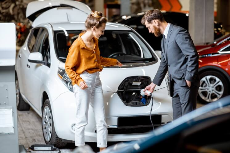 Sales manager with client near electric car at a car dealership