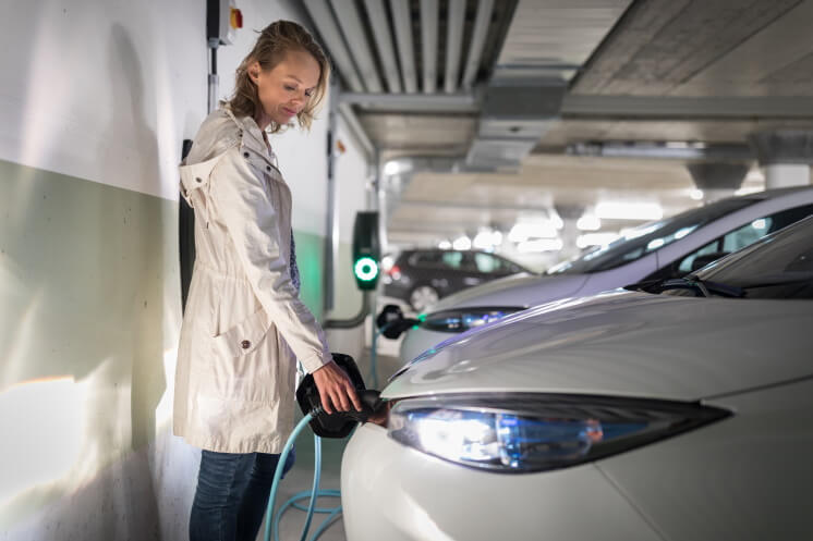 Young woman charging an electric vehicle in an underground garage equiped with e-car charger
