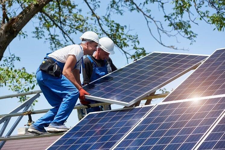 Men installing solar panels on a roof
