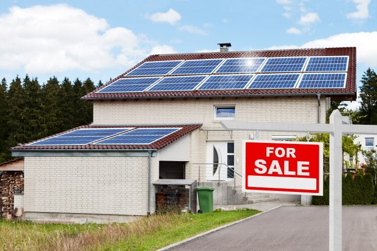 solar panels on a home with a for sale sign